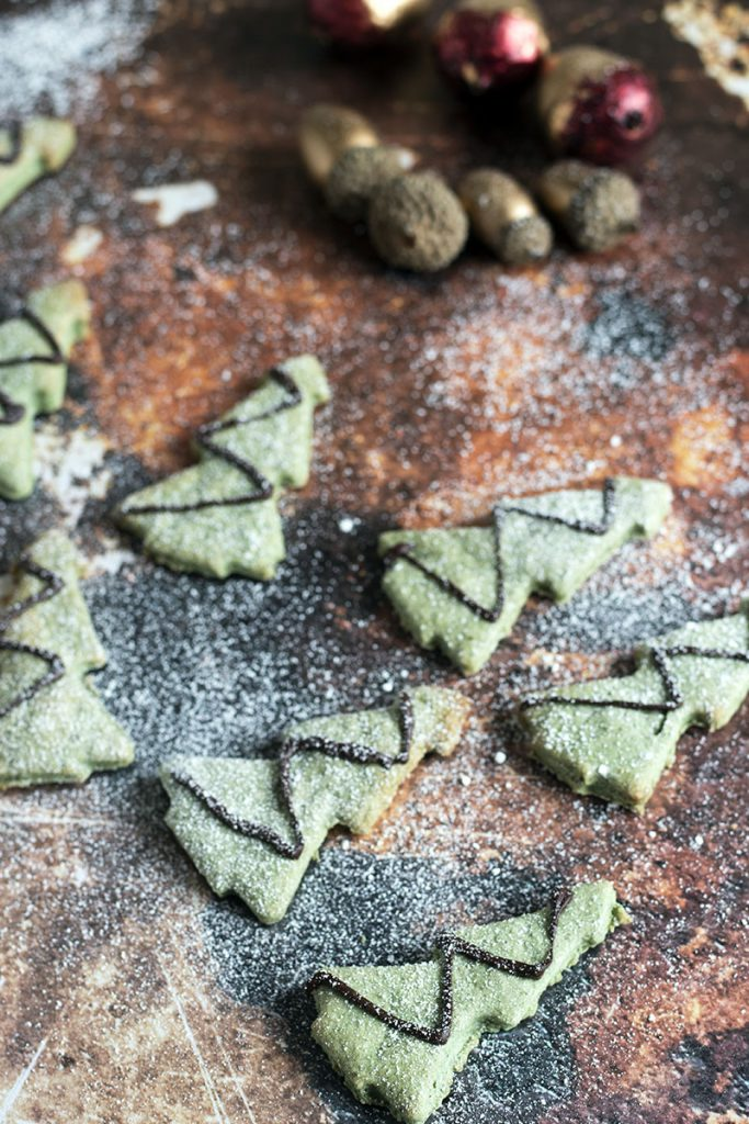 green christmas tree cookies with icing sugar snow and christmas decorations