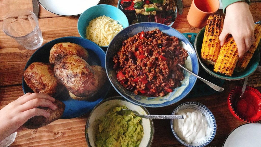 child's hands helping themselves to baked potatoes and corn with vegan chilli