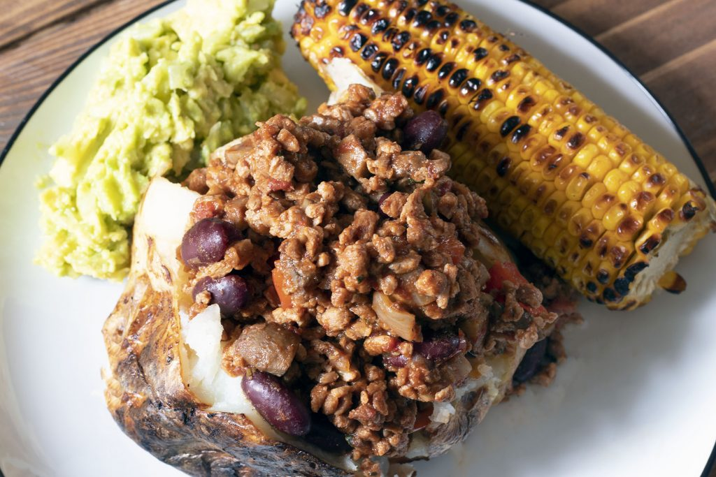 baked potato with veggie chilli, grilled corn and guacamole on white plate