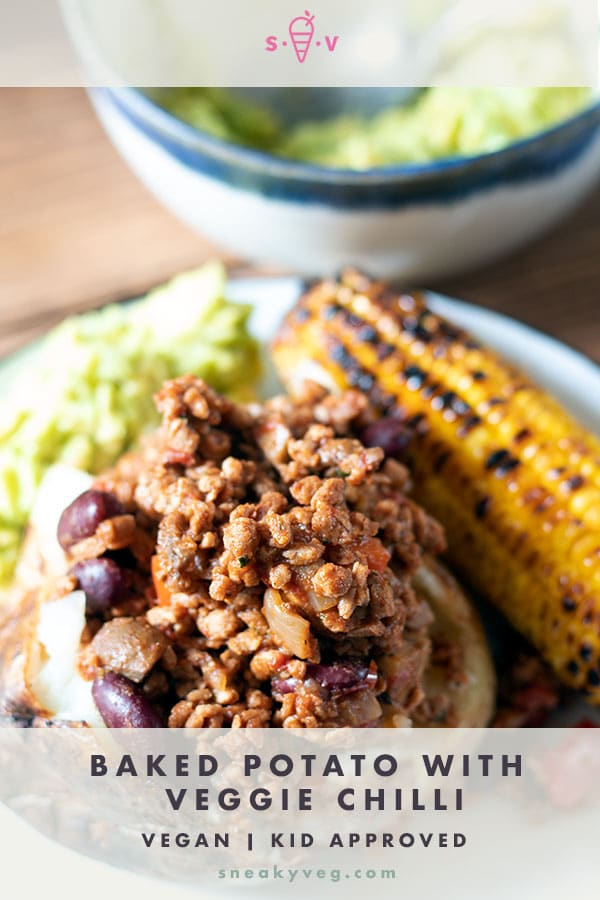 baked potato on white plate with chilli, corn and guacamole