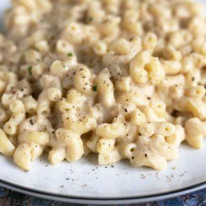 close up of vegan macaroni cheese with cauliflower on white plate