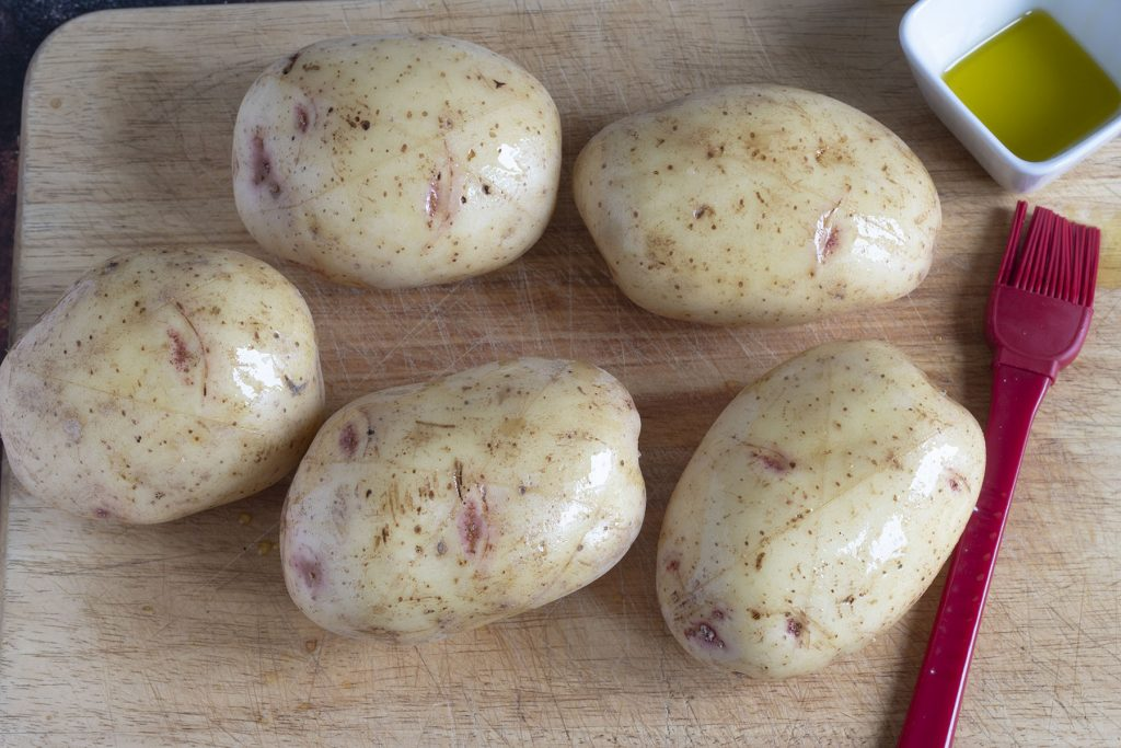 five jacket potatoes brushed with oil