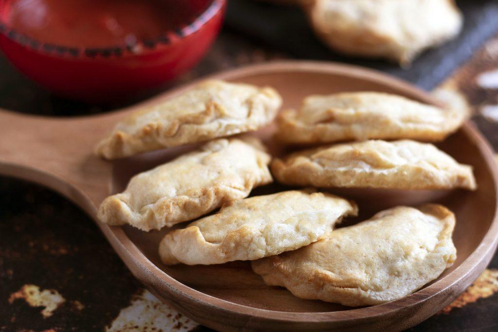 empanadas caprese on wooden plate