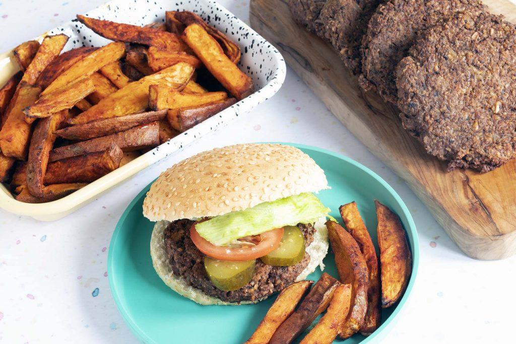 Mushroom burger with sweet potato wedges on blue plate