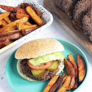 vegan mushroom burgers with sweet potato wedges on blue plate