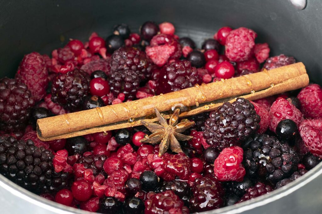frozen berries, maple syrup, star anise and cinnamon stick in saucepan