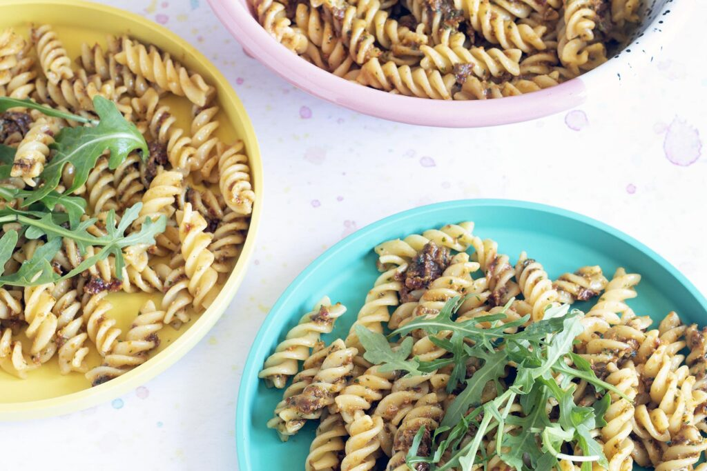 sundried tomato pesto with pasta and rocket on colourful plates