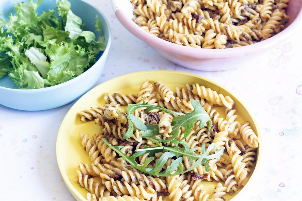 yellow plate with sundried tomato pasta pesto and rocket, bowl of lettuce in background