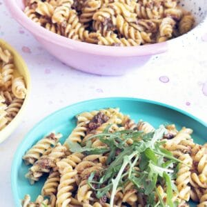 sundried tomato pasta pesto topped with rocket on colourful plates
