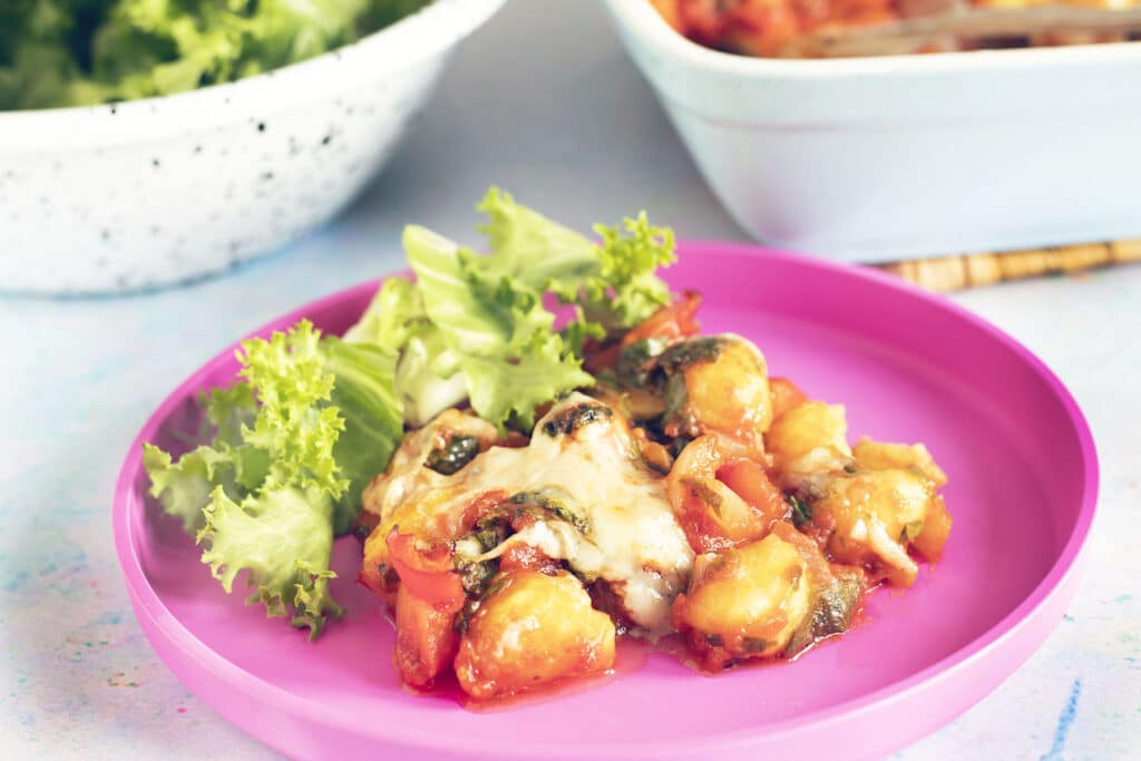 gnocchi bake and salad on pink child's plate