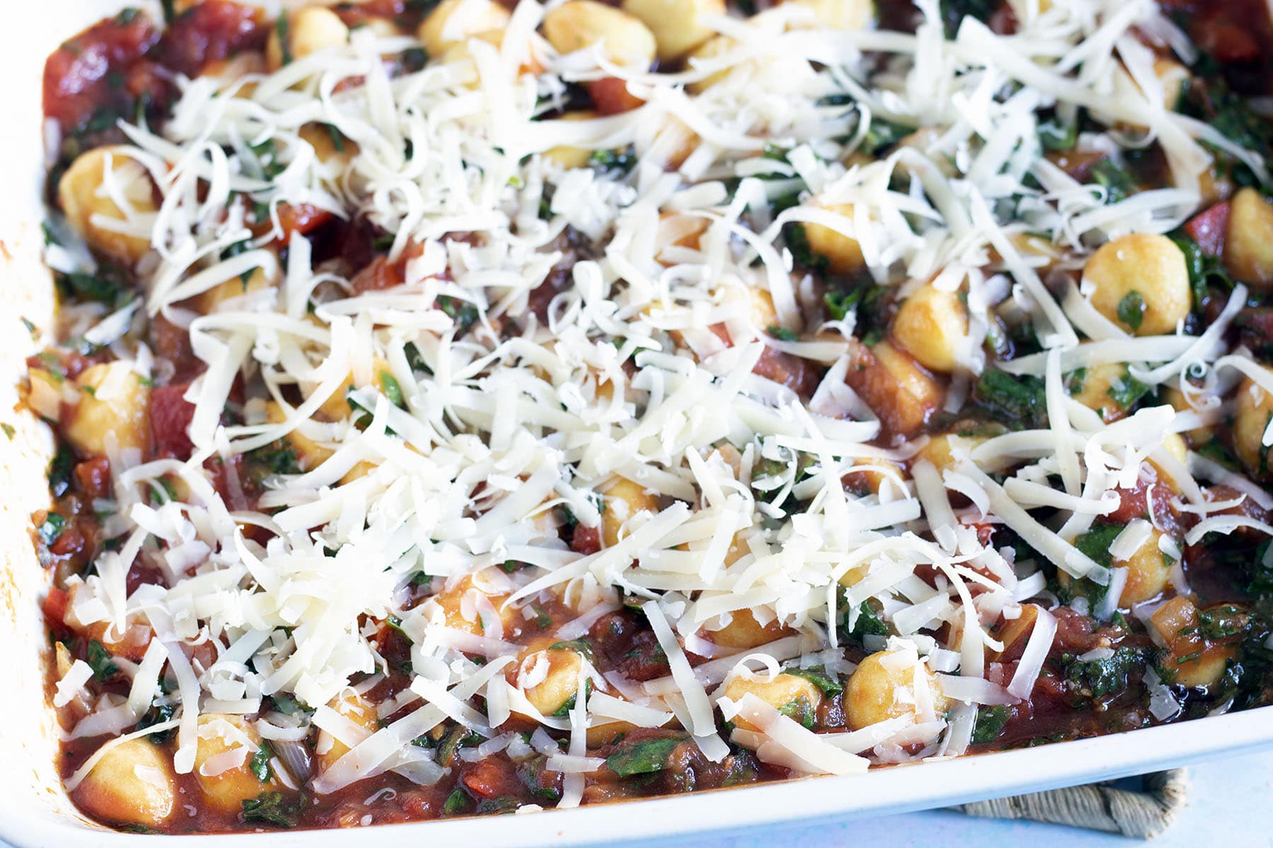 unbaked gnocchi in roasting dish with tomato and spinach sauce topped with grated cheese