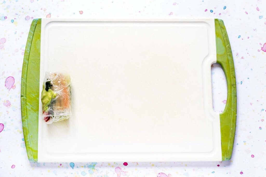 rice paper wrapper partially rolled on chopping board