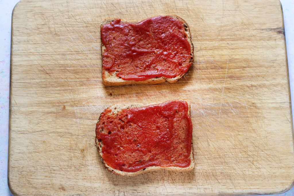 two slices of toast topped with tomato sauce