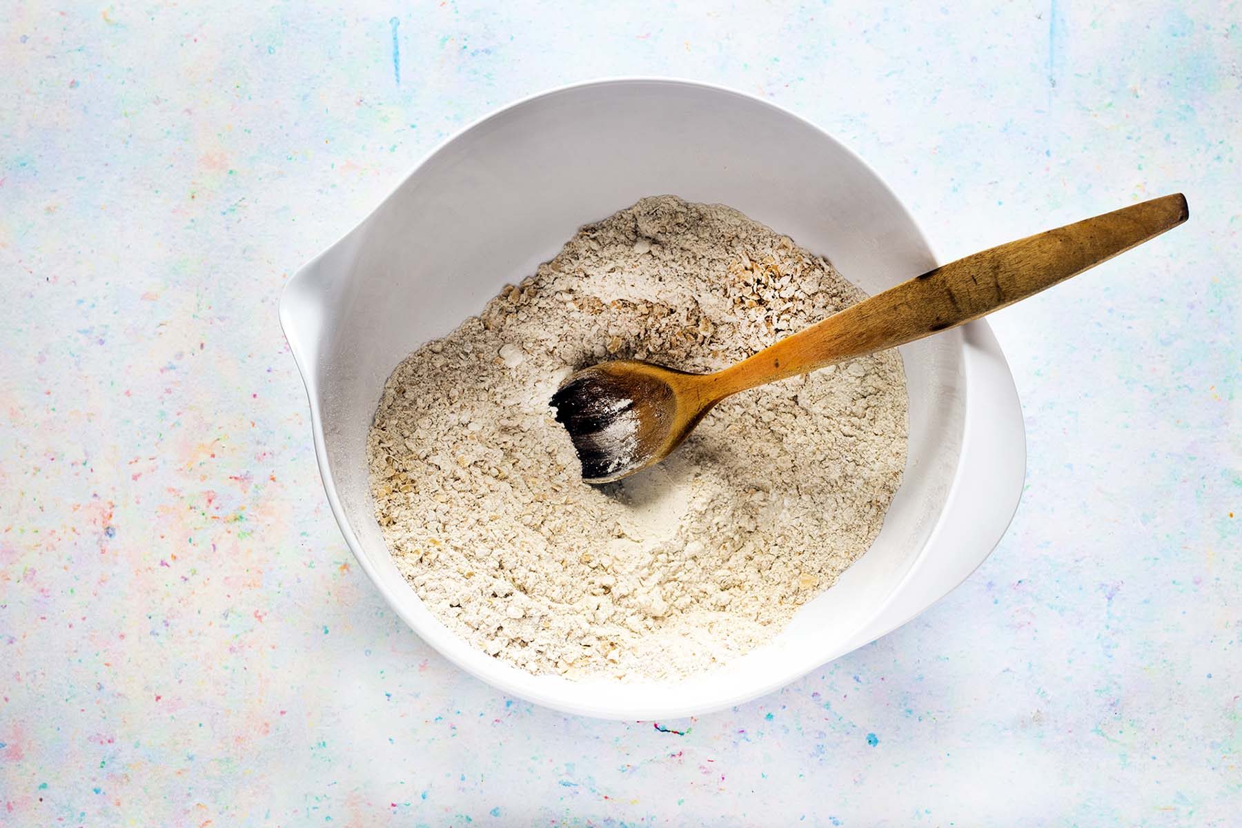 flour and oats in white bowl iwth wooden spoon