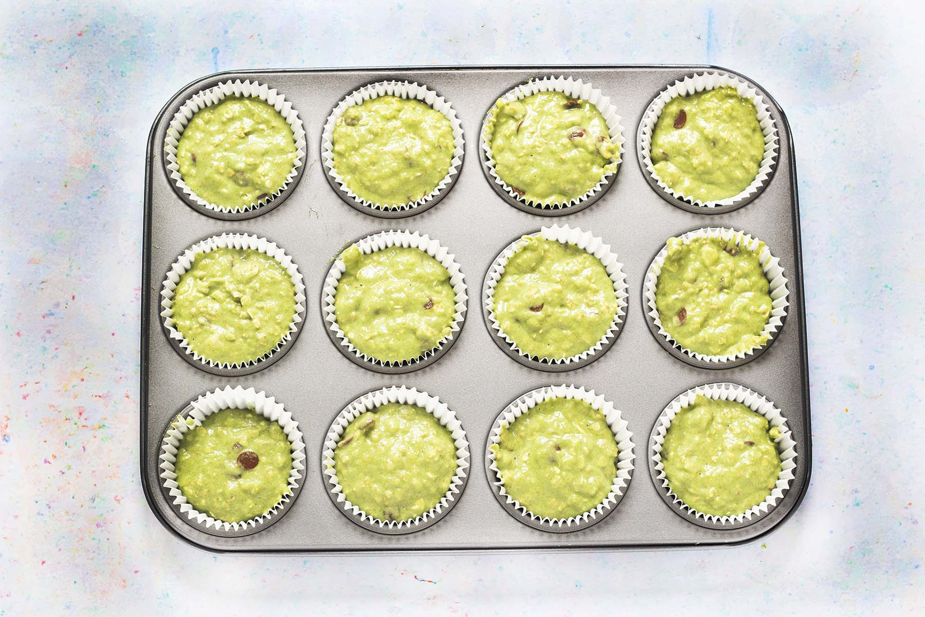 uncooked spinach and banana muffins in muffin tin