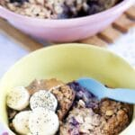 blueberry baked oats in yellow bowl with bananas, nut butter and seeds